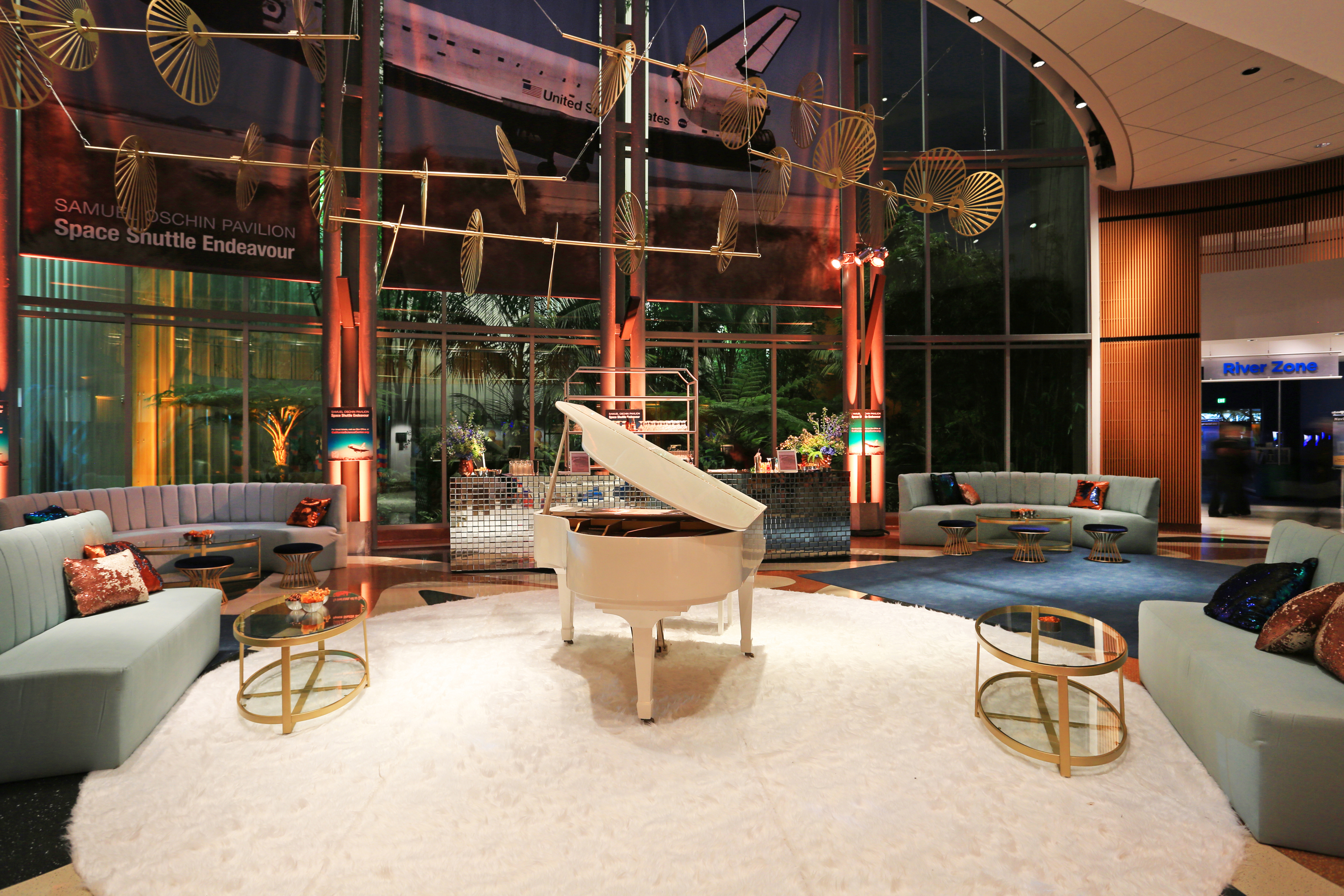 Ecosystems atrium with plush lounge furniture and white piano for private event