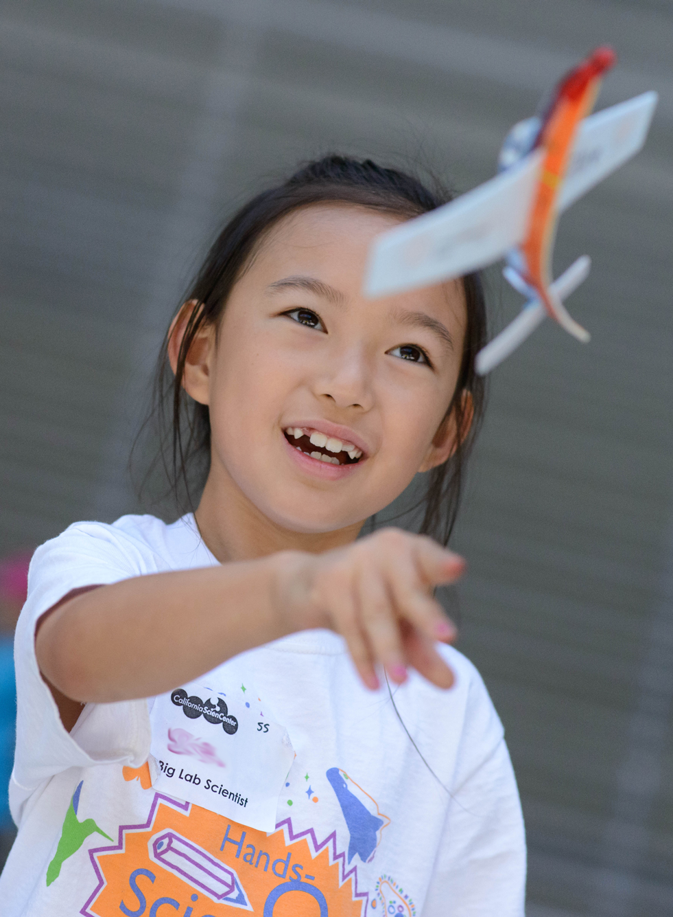 Girl throwing plane, while attending Hands-On Science Camp