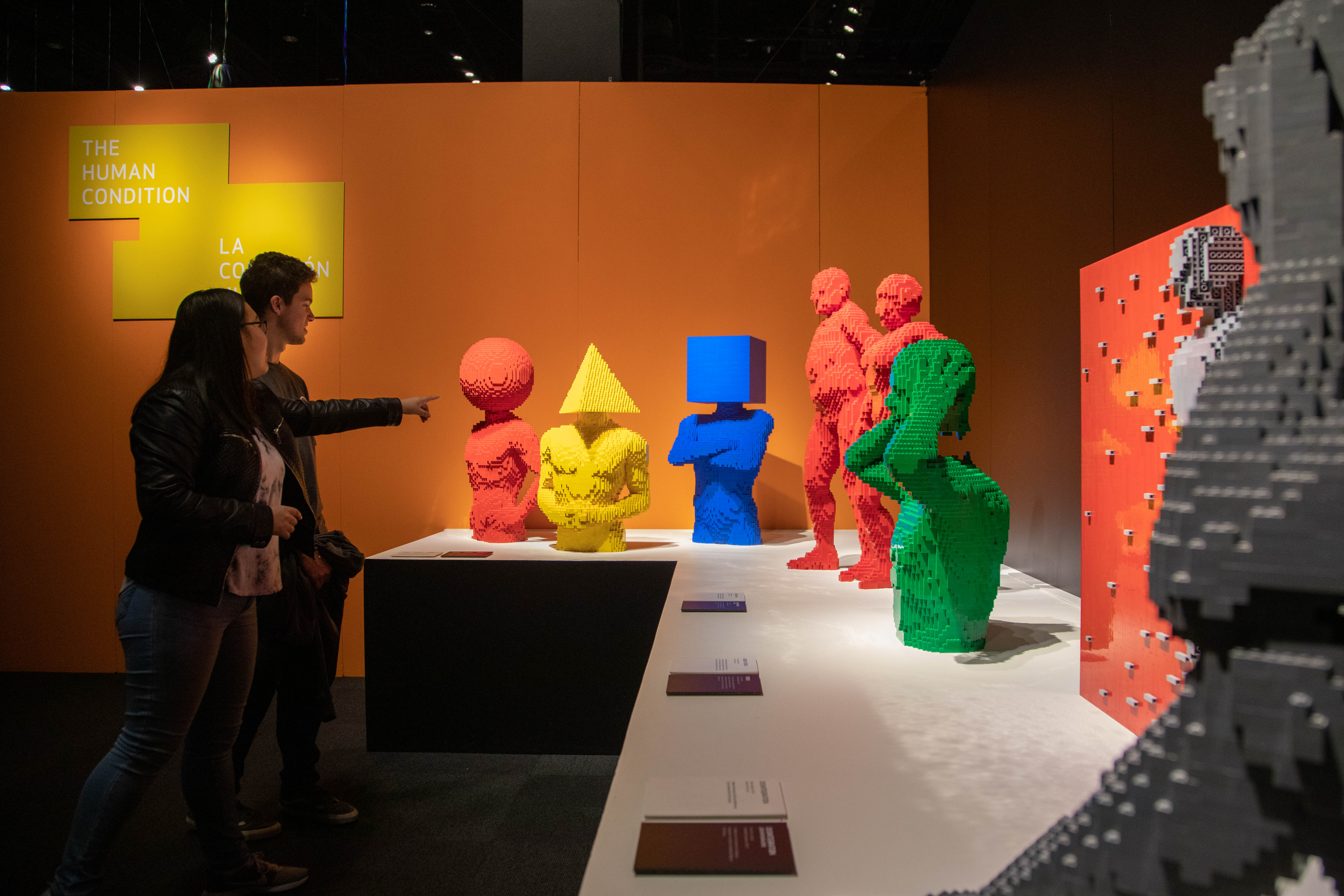 Visitors viewing shape sculptures in The Art of the Brick exhibition