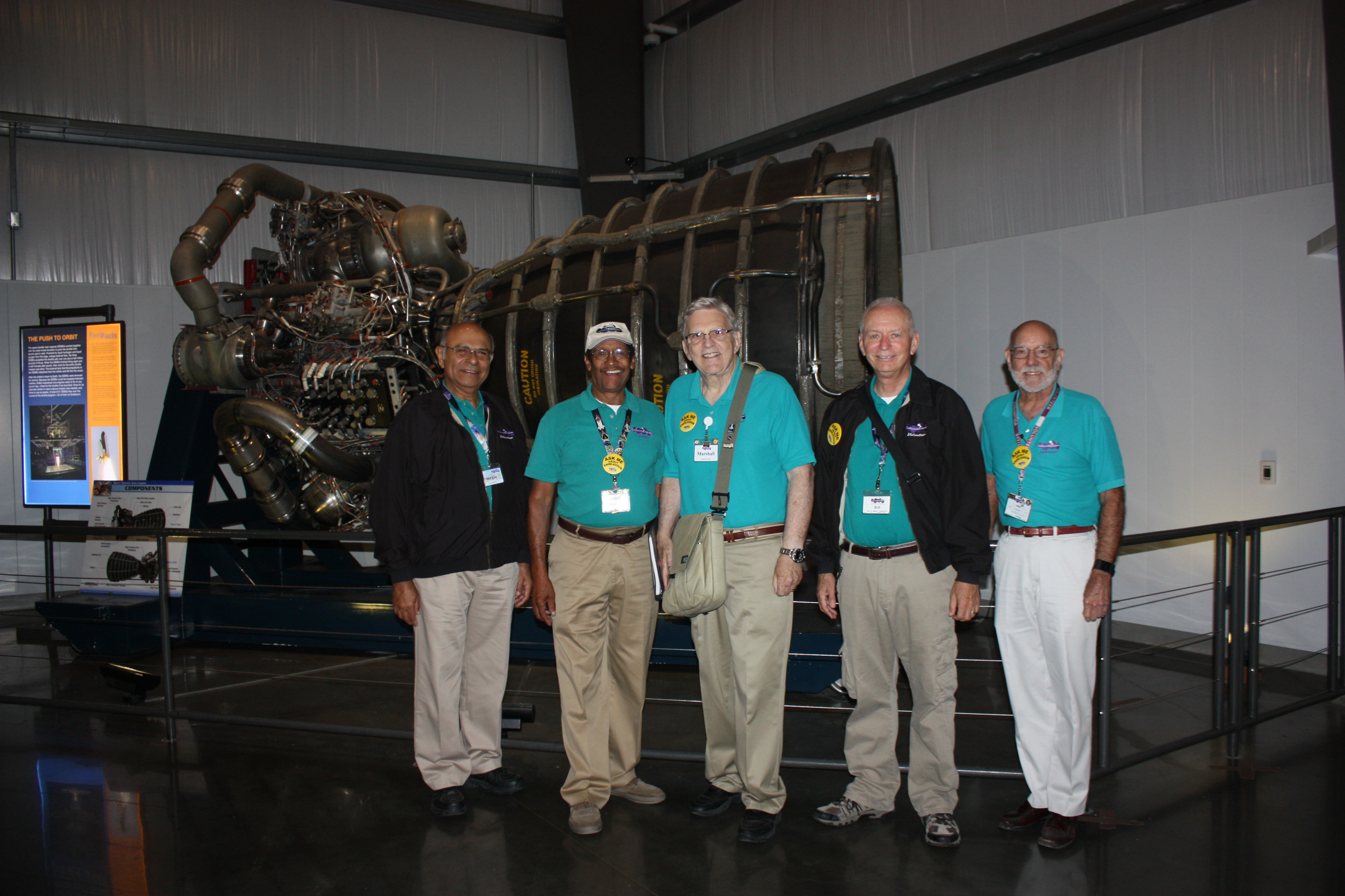 Five Air & Space Volunteers in teal polos and khaki pants uniforms pose in front of Space Shuttle Main Engine on display in the Samuel Oschin Pavilion