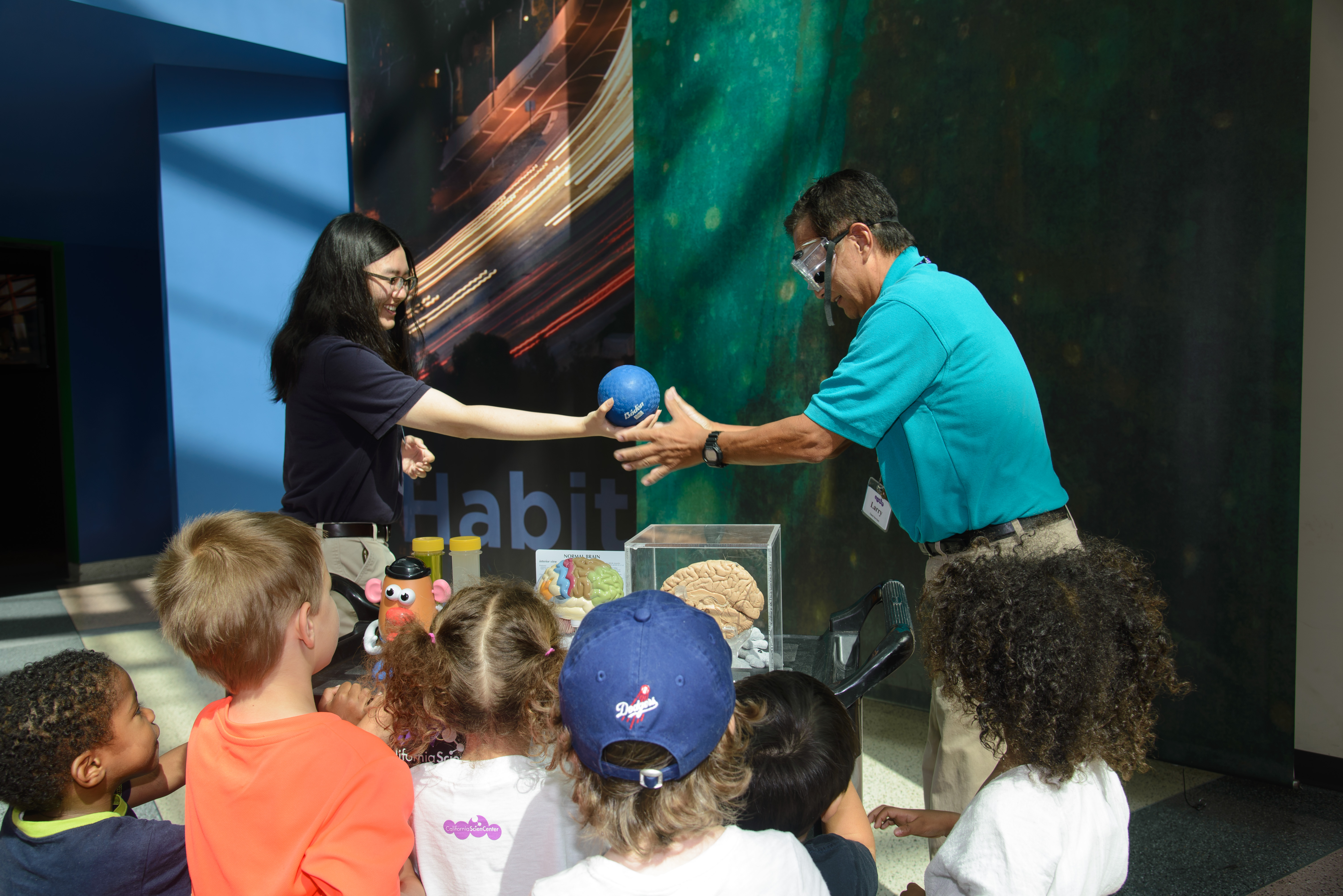 cation team member and Volunteer demonstrate science concept at a cart by passing each other a small blue rubber ball while group of kids watch