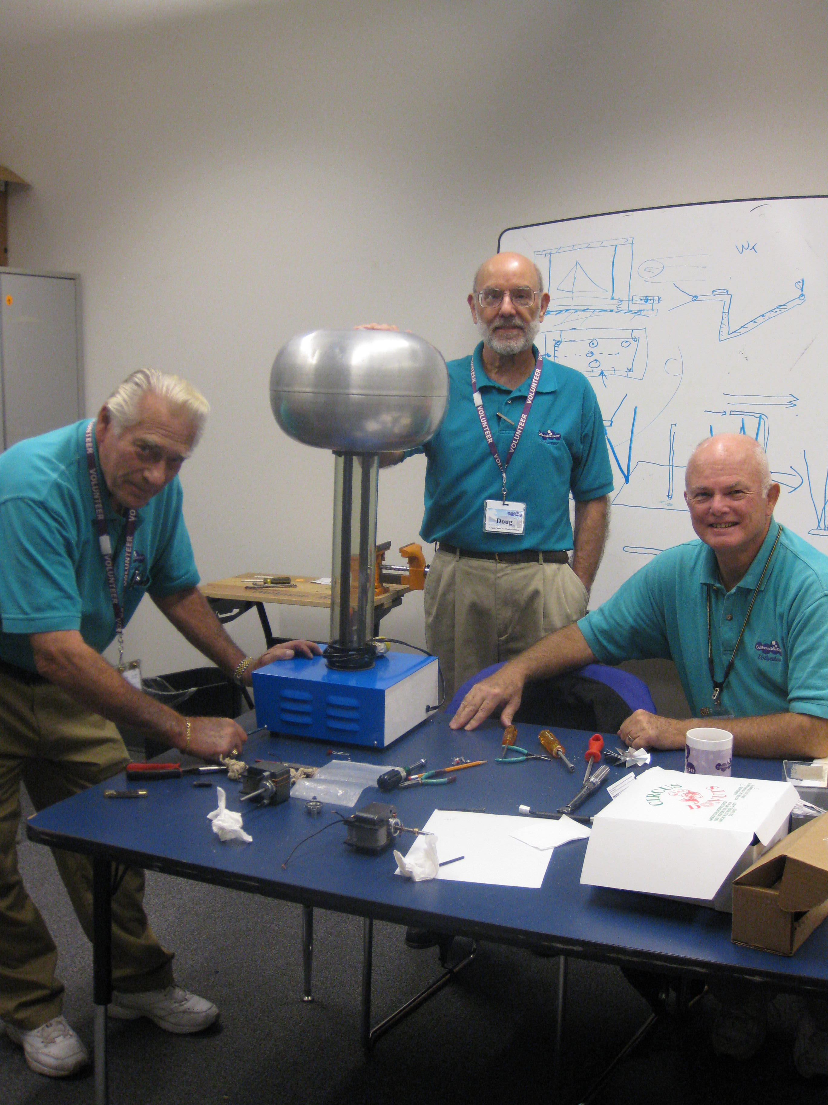 Three Air & Space Volunteers wearing teal polos stand around table with tools and parts while working on Van der Graaf Generator