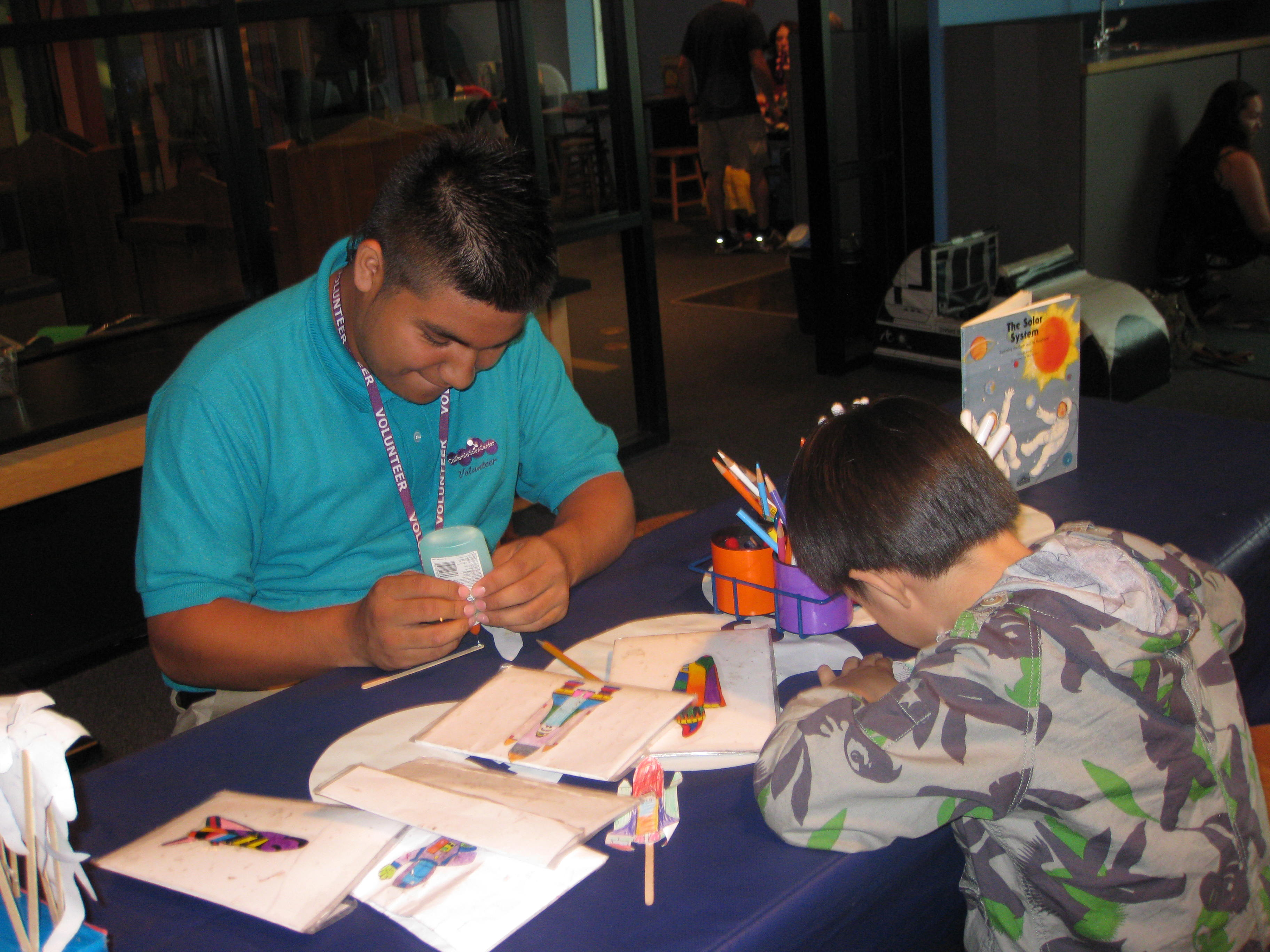 Discovery Room Volunteer wearing teal polo glues Endeavour craft with participating child