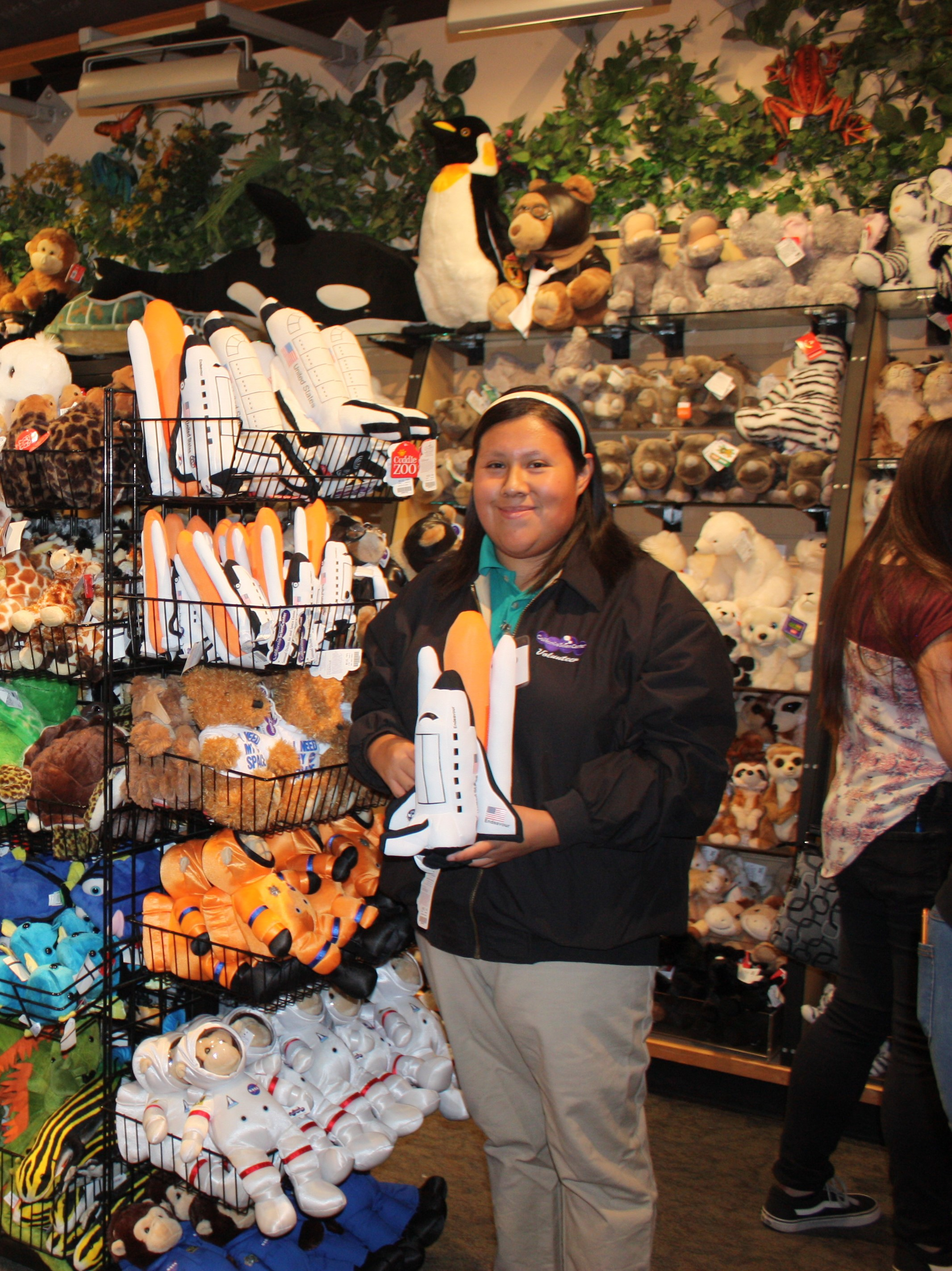 ExploraStore Volunteer holds plush Endeavour Toy next to retail rack of space themed plush toys inside the store.