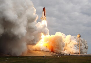 Space shuttle Endeavour roars off the launch pad in a cloud of steam and smoke.