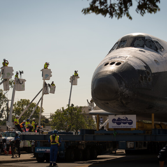 Endeavour on a Los Angeles street, with workers in lifts to get a better look at the scene