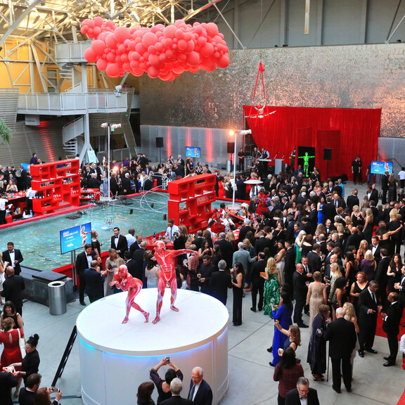 Discovery Ball cocktail party in the Wallis Annenberg Building adorned with elevated red balloon sculpture and BodyWorlds inspired dancers