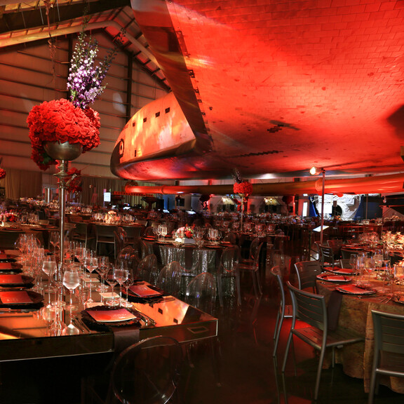 Mirrored dining table with tall red florals under the wings of the Space Shuttle Endeavour for a fundraising gala