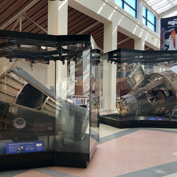 One Mercury, one Gemini, and one Apollo space capsule, each on display in its own glass case