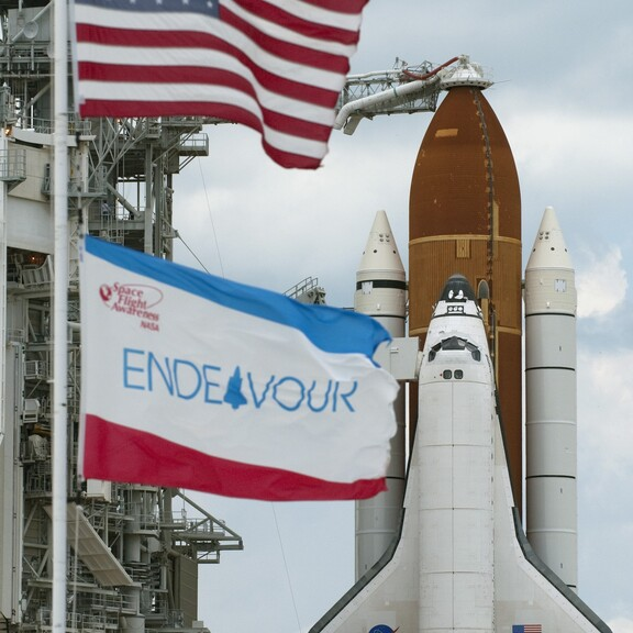 Space Shuttle Endeavour on the launch pad, with the American flag and an Endeavour flag in the foreground