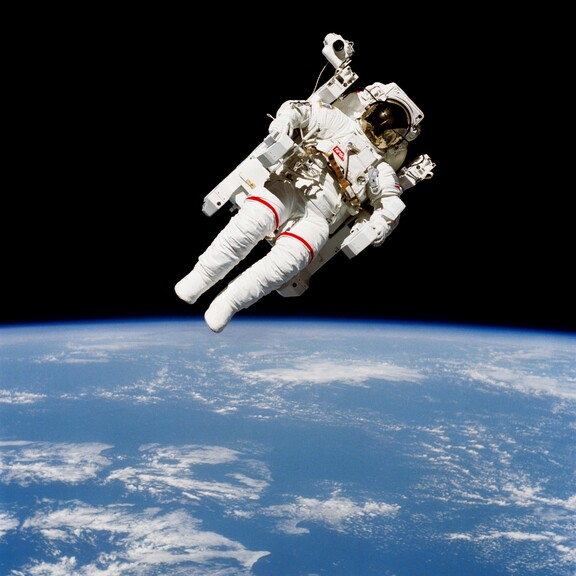 An astronaut in a spacesuit floats untethered above Earth.