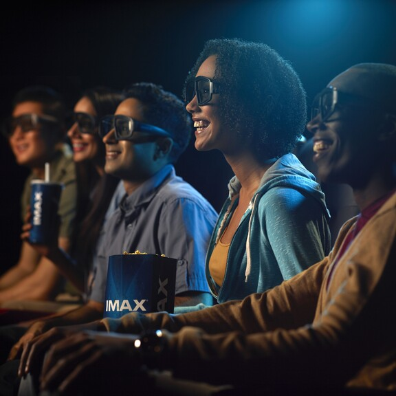 Visitors wearing 3D glasses in their seats watching an IMAX movie
