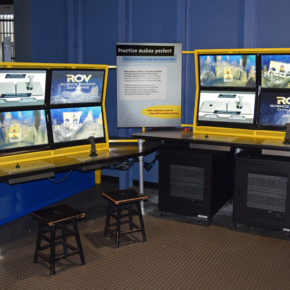 Two screen-based remote-operated vehicle simulation stations, each paired with two joysticks