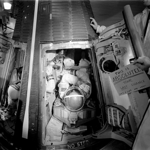 Conrad (left) and Gordon (center) are inserted into their couches aboard Gemini XI on launch morning. A sign reads 'This is absolutely your last chance. CM3 & CM4 are next.'