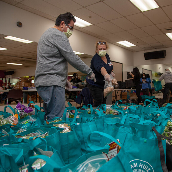 Volunteers wearing masks pack up teal reusable grocery bags with food to be distributed to families in need