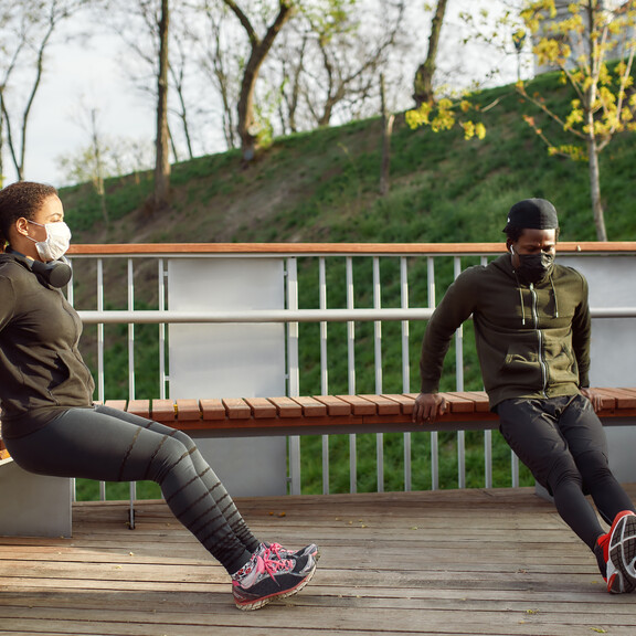 An African-American man and woman exercise outdoors while wearing face masks and staying six feet apart