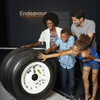 A diverse family touches space shuttle tires in an Endeavour exhibit.