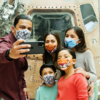 Family with face coverings takes a selfie in front of an Apollo space capsule