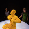 Guests in The Art of the Brick exhibit view Yellow Man, a life-size sculpture of a man ripping his chest open with thousands of yellow LEGO bricks cascading out
