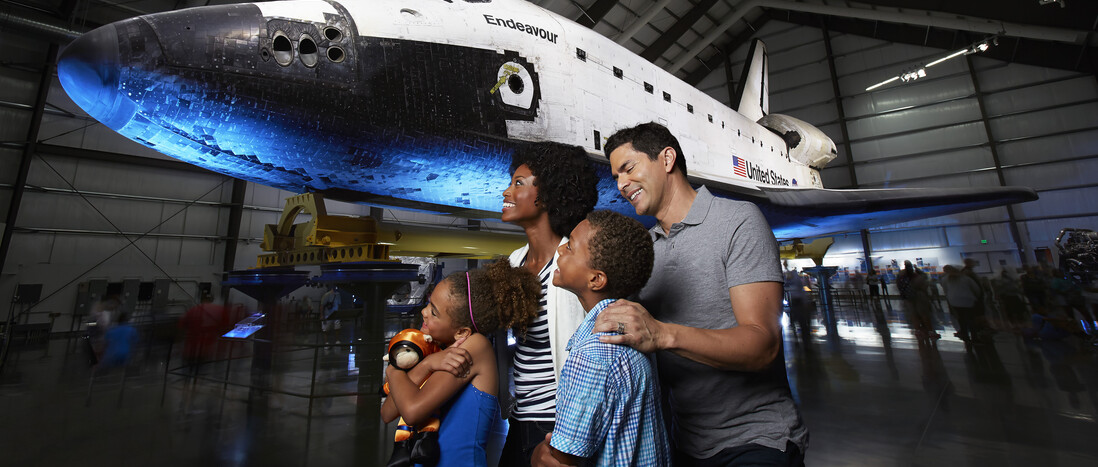 A diverse family group enjoys the space shuttle Endeavour display in the Samuel Oschin Pavilion.