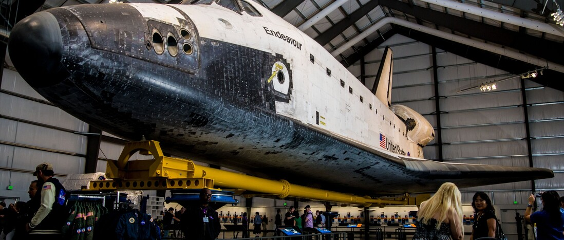Guests walk around and under admiring space shuttle Endeavour on display at the California Science Center.