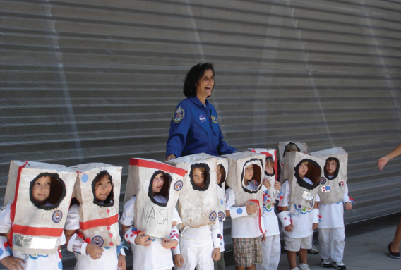 Young kids dressed as astronauts standing in front of NASA astronaut
